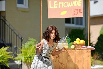 child making sour face holding lemon