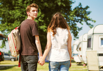 Teenage couple walk touching hand in hand