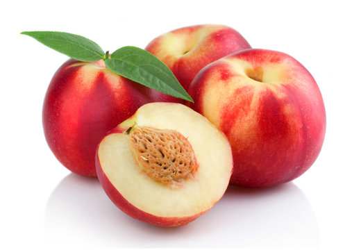 Three ripe peach (nectarine) fruits with slices isolated