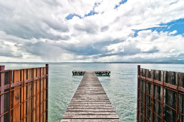 pier and cloudy dramatic sky over Garda lake - Italy