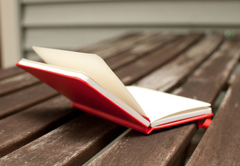 Red notebook open on wooden table