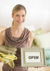 Female Owner Holding Sheets And Open Sign In Bedding Store