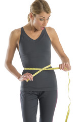 Surprised Young Woman Measuring Her Waistline