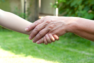 hands of young child and old senior outside