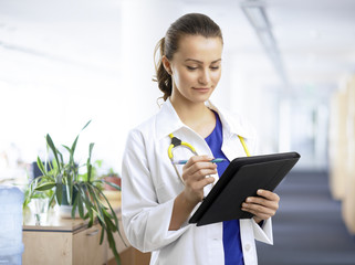 Beautiful female doctor examining the patient chart