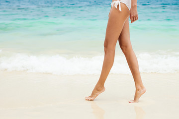 Walking on the beach. Close up on legs walking along the sea sid
