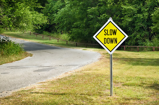 Slow Down yellow traffic sign on the roadside against woods