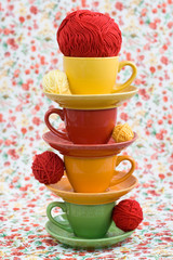 Four colorful cups and balls of yarn on a background