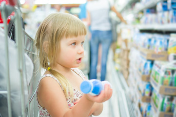 Adorable girl select milk products in supermarket. Holding small