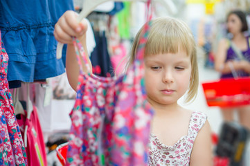 Adorable girl select light dresses in cloth department in superm