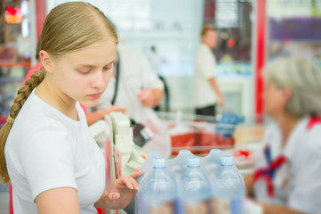 Young woman at cash desk in supermarket with bottles of water