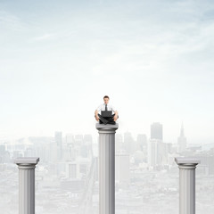 businessman sitting on column