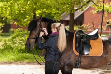 Mädchen zäumt ihr Pferd