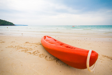 Orange kayak on a beach.