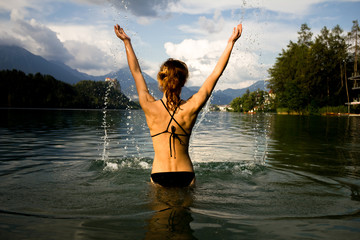Woman splashing around in a mountain lake