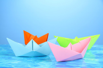 Paper ships of different colors on water background