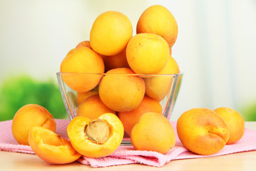 Fresh natural apricot in bowl on table in kitchen