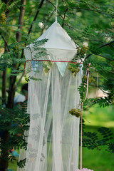 in the park in the summer on a tree weighs white tulle tent