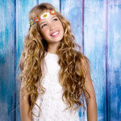 Blond happy hippie children girl smiling on blue wood