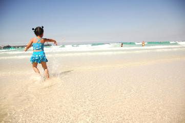 Happy little girl having fun on the beach