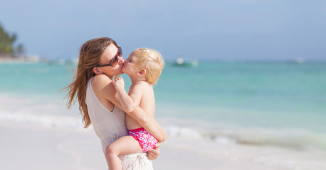 Mother and little daughter kissing on the beach