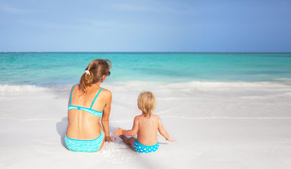 Mother and little daughter sitting on the beach