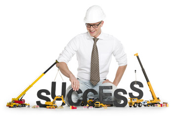 Working on success: Businessman buildinging success-word.