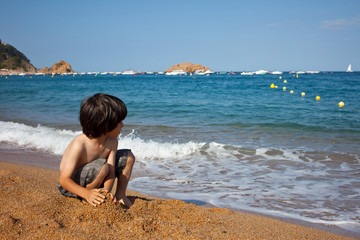 boy on the shore of  sea
