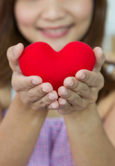 Closeup heart shape with women's hands in vertical