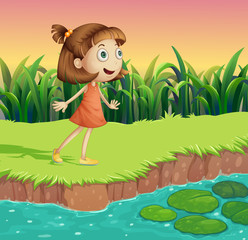 A small girl at the riverbank