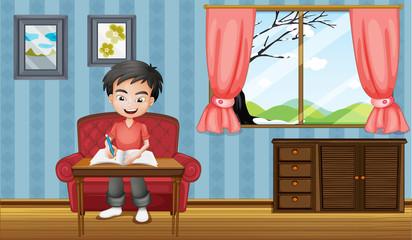 A boy writing inside the house
