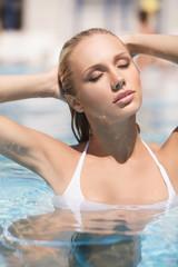 Hot summer day. Attractive young women in bikini relaxing in poo