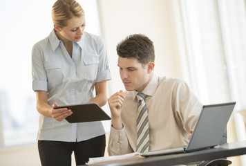 Business People Discussing Over Digital Tablet In Office