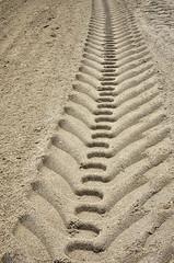 Wheel track on sand background