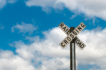 Railroad Crossing Sign Against Cloudy Sky