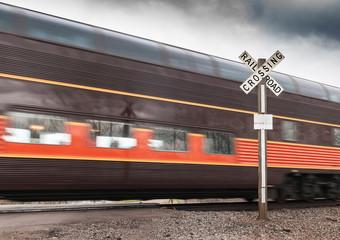 Brown Passenger Car Flies by Railroad Crossing