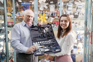 mature man and woman holds  automotive   tool set