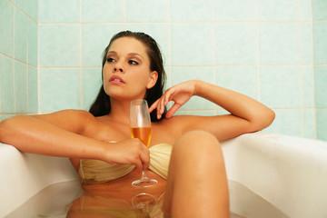 Model trinkt Champagner in der Badewanne