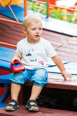 Child walking in the park with a toy