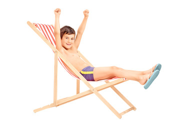 Happy boy sitting on an outdoor chair with raised hands