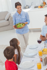 Woman bringing a salad to her family