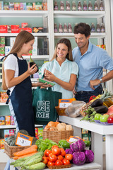 Saleswoman Showing Vegetable Packet To Couple