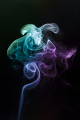 multicolor smoke rises up on a black background.