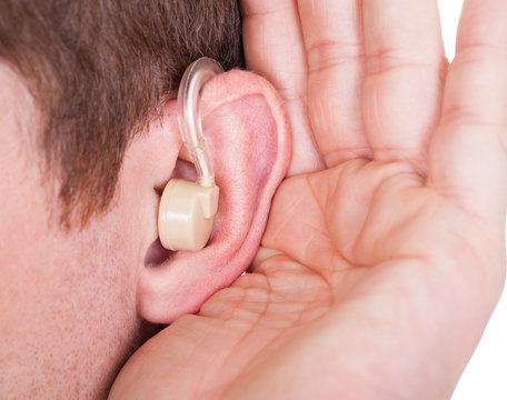 Man Wearing Hearing Aid And Listening For A Quiet Sound