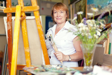 woman artist paints the flowers on canvas