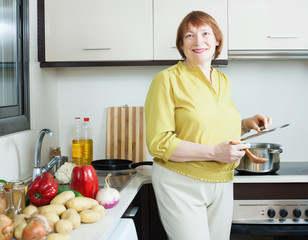 Positive mature woman with pan