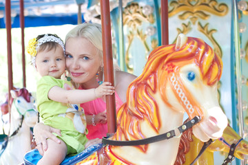Happy mother and daughter on carousel