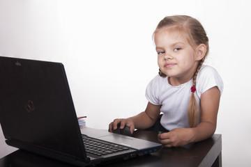 Девочка работает за ноутбуком, отвлеклась и посмотрела в кадр
