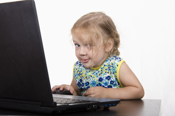 Девочка работает за ноутбуком и загадочно посмотрела в кадр