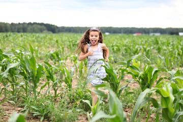 Joyful little girl running through the corn field